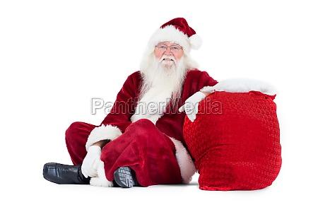 der weihnachtsmann sitzt neben seiner tasche