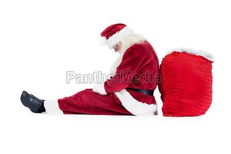 der weihnachtsmann sitzt auf seine tasche