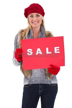 blond im winter kleidung mit verkaufszeichen