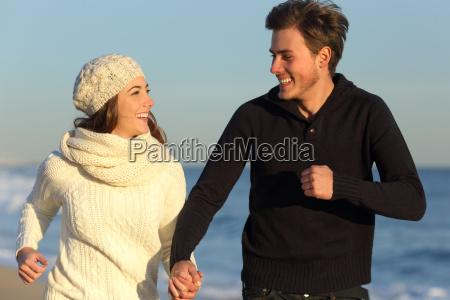 coppia in esecuzione sulla spiaggia in