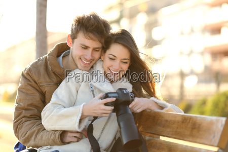 couple of tourists reviewing photos in
