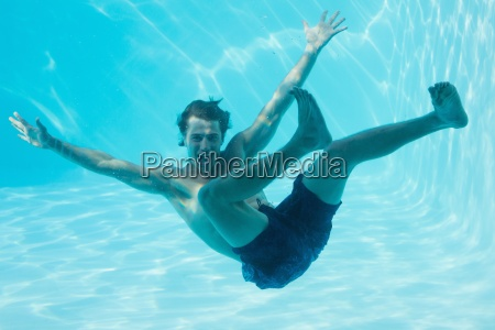 junger mann schwimmt unter wasser