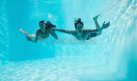 ehepaar haelt haende und schwimmt unter