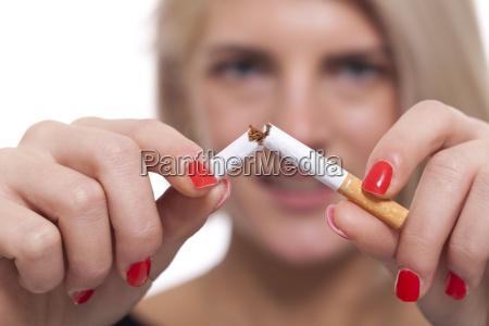 junge blonde frau zerbricht eine zigarette