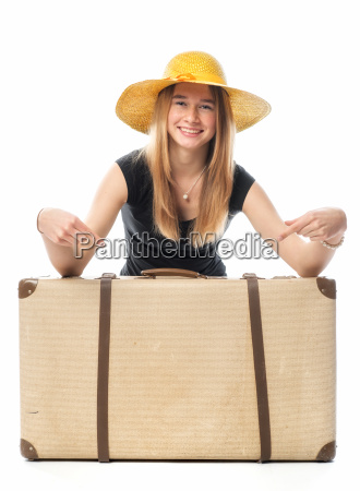 young girl squats behind a suitcase