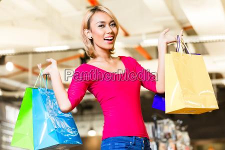 asiatische junge frau beim einkaufen mode