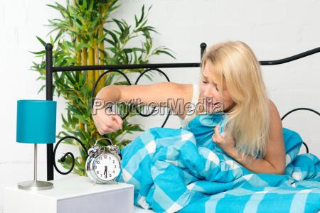 woman bed time awakening clock alarm