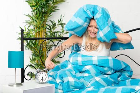 woman bed time irritated clock alarm