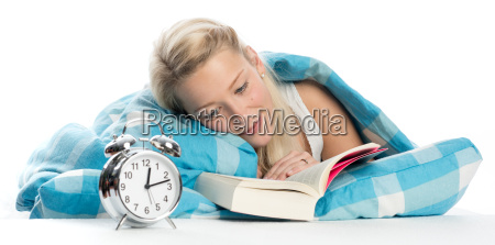 blond woman lying in bed reading