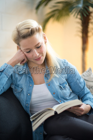 blonde woman sitting on the sofa