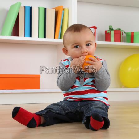 kleines baby isst eine orange frucht