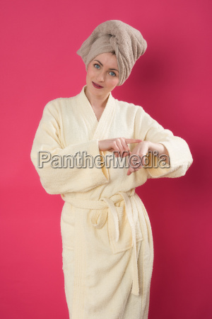 woman in bathrobe putting lotion on