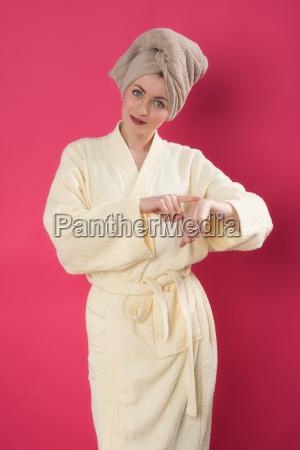 woman in bathrobe putting lotion on
