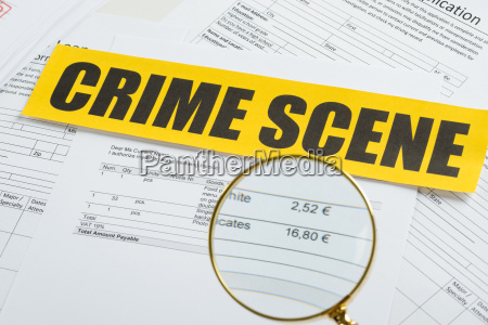 magnifying glass over documents with crime