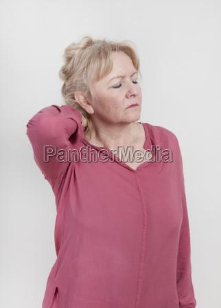 aeltere frau mit nackenschmerzen
