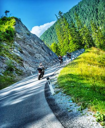 bikers tour along alps
