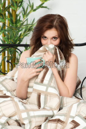 young woman sitting cuddled in bed
