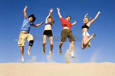 vier junge erwachsene springen auf einer