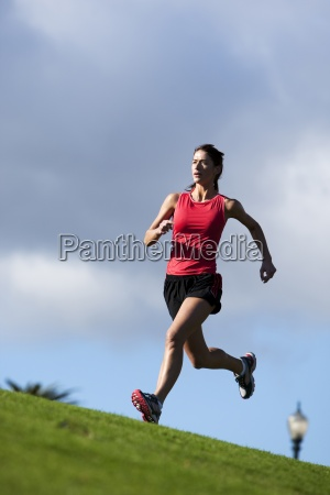 an athletic woman running along the