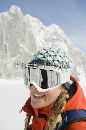 eine junge frau skifahrer laechelt in