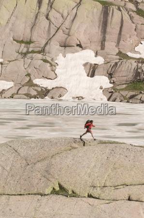 a woman backpacker jumping across a