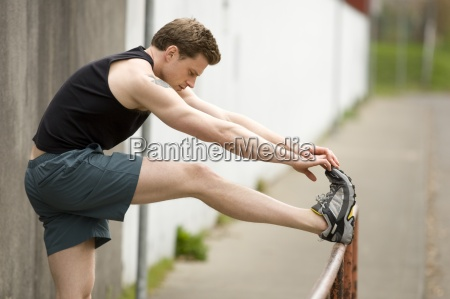 ein athletischer mann streckt sich vor