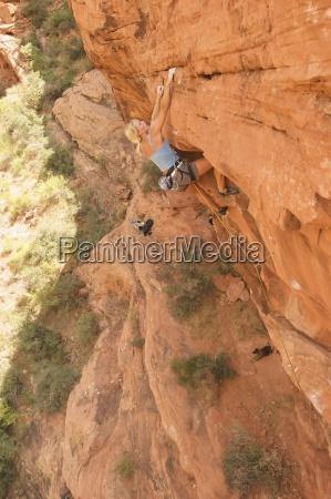 ein rock kletterer steigt eine rote