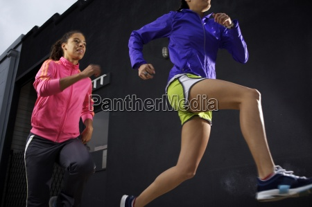 two female runners being competitive in
