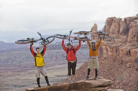 drei junge maenner halten ihre fahrraeder