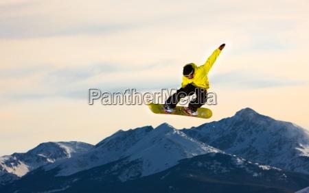 springender snowboarder fliegt durch die luft