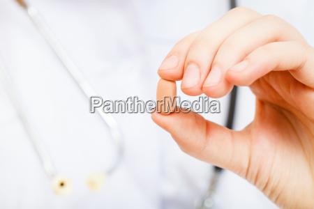 krankenschwester haelt tablette in den fingern