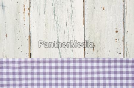 violett kariertes tischtuch vor weissem holzhintergrund