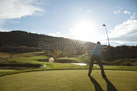 ein golfer faehrt bei sonnenuntergang in