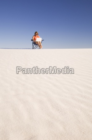 woman using laptop in the sand