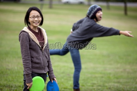 two young asian american women play