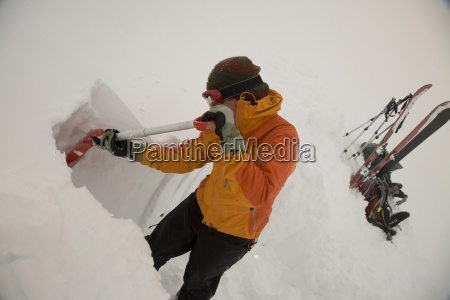 a male backcountry skier digs out