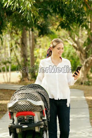 mother with baby in pushchair sending