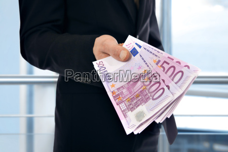 a businessman holding money euro