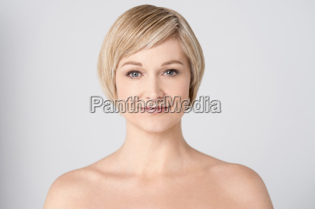 topless woman smiling over grey