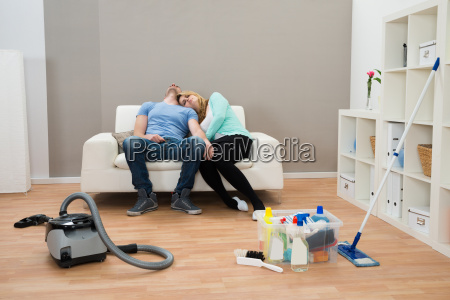 exhausted couple on sofa in living