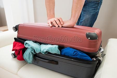 person hand versucht koffer zu schliessen