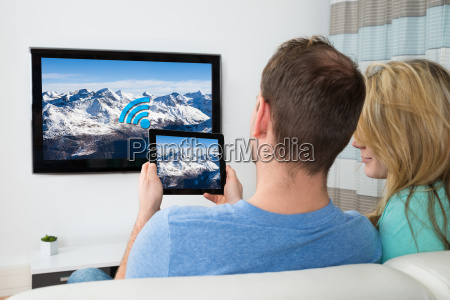 couple with digital tablet and television