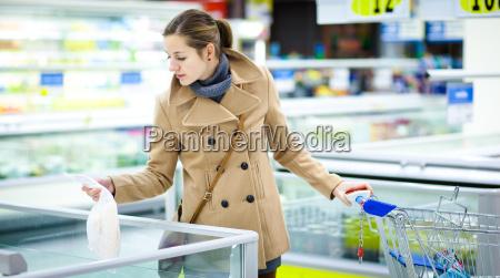 schoene junge frau beim einkaufen fuer
