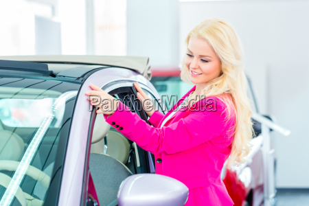 frau sucht neuwagen im autohaus aus