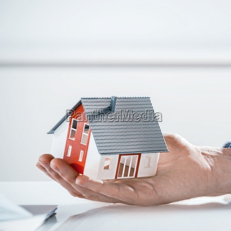bare hand holding miniature architectural house