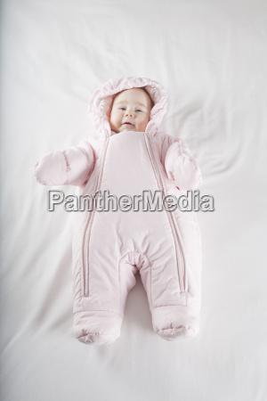rosa snowsuit baby auf dem bett