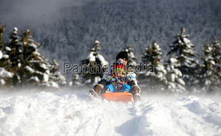 a little boy sledging in the