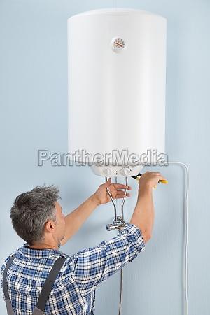 male plumber repairing electric boiler