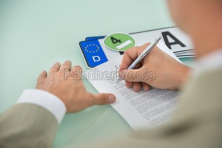 businessman filling car sale contract form