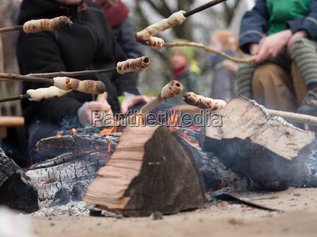 familie grillt stockbrot ueber offenem feuer